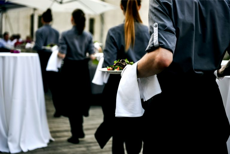 A line of catering personeel bringing food to guests of a very beautiful wedding reception
