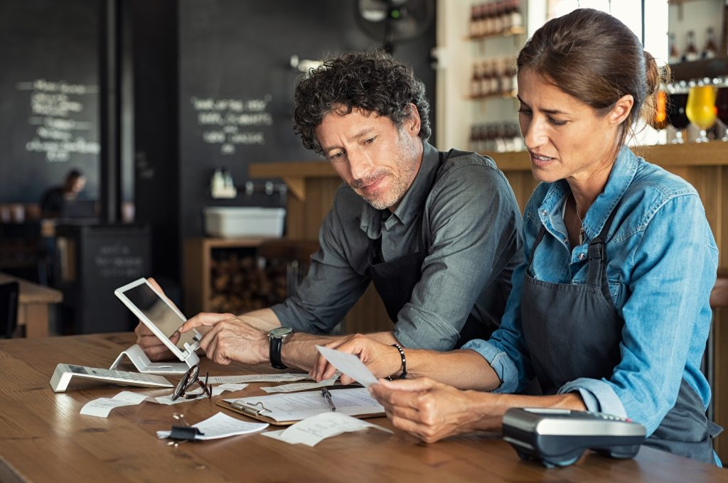 Man and woman sitting in cafeteria discussing finance for the month. Stressed couple looking at bills sitting in restaurant wearing uniform apron. Café staff sitting together looking at expenses and bills.