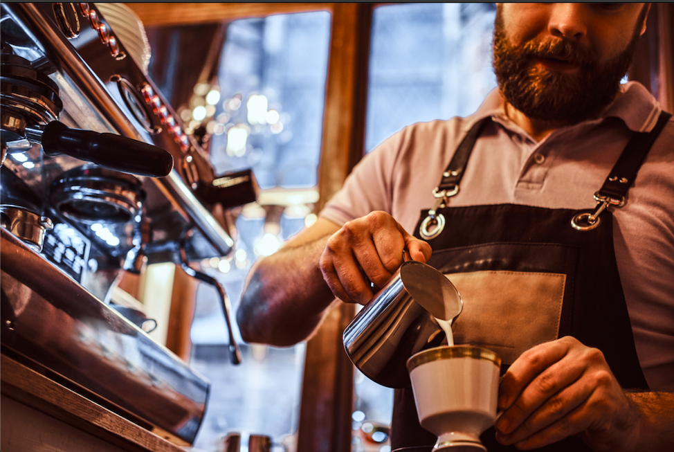 Barista that works for Horeca Uitzendbureau Amsterdam pouring coffee for a customer