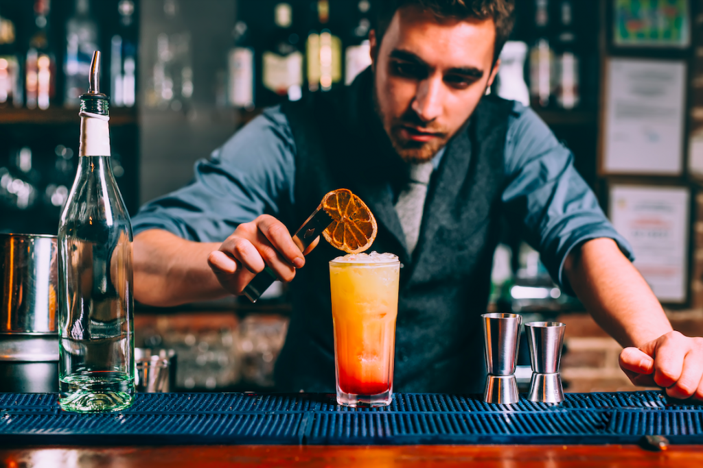 Bartender places Orange slice on top of a drink he has prepared for a customer